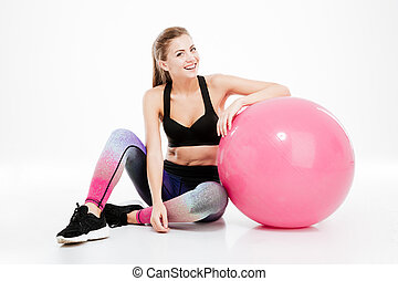 Fitness girl with pink ball sitting and looking at camera -...