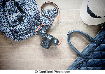 Flat lay photography with camera, travel accessories, essential items for woman, Overhead view, top view on wood background