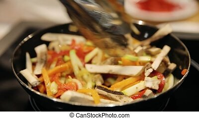 pasta cooking roast vegetables in a pan in a restaurant -...