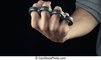 Placing knuckle-duster on the hand male fist with brass...