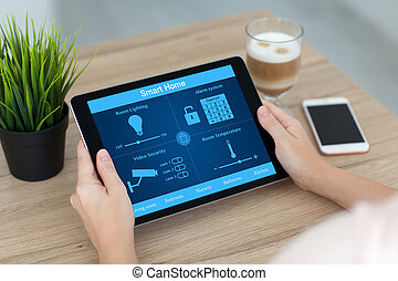 woman holding tablet computer with smart home near phone...