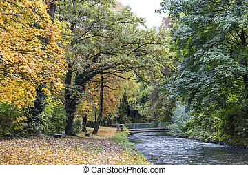 beautiful river Wuerm with green trees in Munich in autumn...