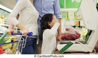 family weighing paprika on scale at grocery store -...