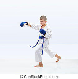 Boy beats a punch arm on a light background