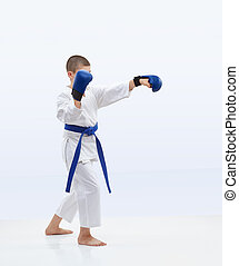 Karateka with a blue belt is training punch arm