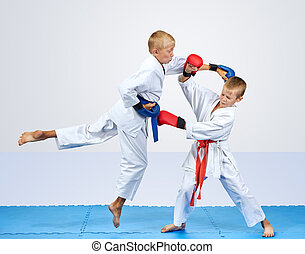 On a blue mats athletes are training punch arm and block