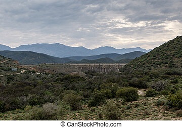 Dam wall at Calitzdorp, cloudy with mountains in the...