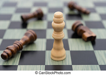 chess board with the white King stands other black ones lay down