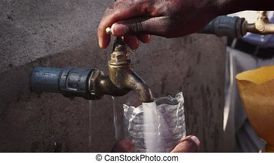 Getting water from a faucet in africa - People getting water...