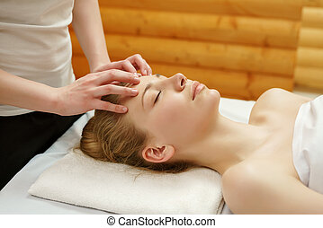 Caring about beauty. Facial massage in spa salon