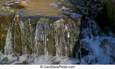 A small waterfall in the park in autumn. Slow motion