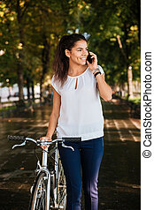 Happy girl talking on the phone and walking with bicycle -...