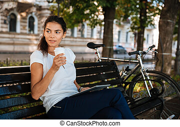 Woman resting on bench with cup of coffee at park -...