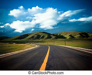 road to the future with the mountain and blue sky background...