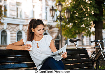Woman reading newspaper while sitting on the bench -...