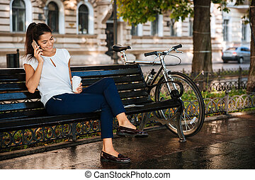 Woman sitting on the bench with smartphone - Beautiful...