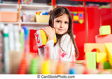 Preschooler child playing with colorful toy blocks