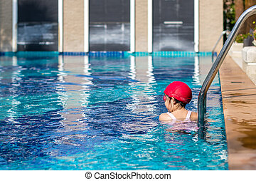 Child Resting at Edge of Swimming Pool After Swimming Training