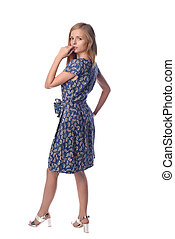 Young pretty long haired blonde woman posing in fashion dress on white background in a studio. Spring summer photo, catalog collection.