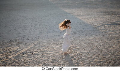 Girl spinning around herself on the sand