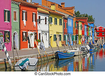 Italy. Burano island  near Venice. Romantic canal with old small colorful houses and boats. Landmark of Veneto region