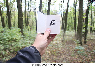 Get Away, book and text - Get Away idea, hand holding a book...