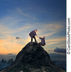 two of asian business man helping hand to climbing up to...