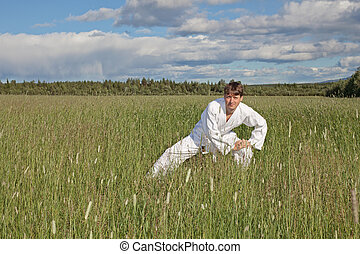 ?oung man practices Wushu in field