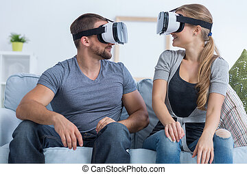 Man and woman wearing VR glasses - Man and woman sitting on...