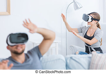 Man and woman using 3D glasses at home