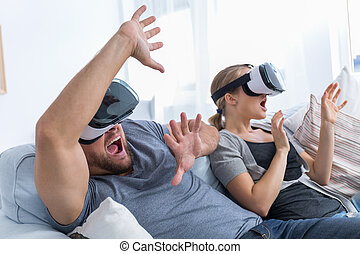 Couple playing videogames in VR glasses - Scared couple...