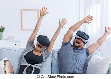 Man and woman wearing VR glasses at home - Young man and...