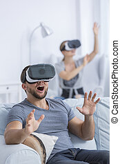 Excited man using 3D glasses playing at light home interior