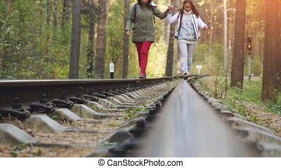 Young women walking together on railroad in pines forest in...