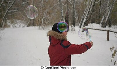 boy makes big soap bubbles in the Park with delight