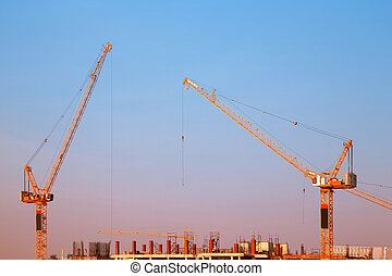 Industrial construction crane during sunset