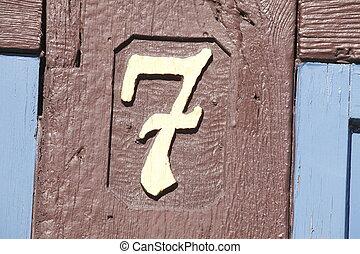 Hausnummernschild - Goldenes Hausnummernschild auf braunen...