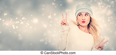 Young woman giving the peace sign in snowy night