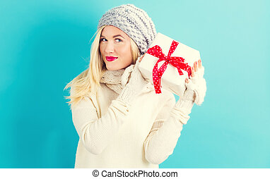 Happy young woman holding a Christmas gift - Happy young...