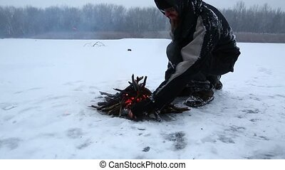 Campfire in winter - Making fire in winter falling snow,...