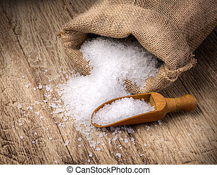 sea salt in the bag and with wooden spoon on wooden...