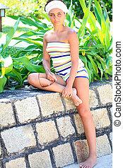 Woman in garden - Young woman relaxing in a tropical garden