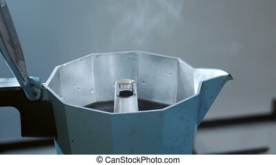 Italian coffee sprinkling out of blue moka coffee-maker...