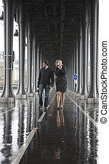 Bad weather in Paris. Couple on the bridge Bir-Hakeim at rainy weather
