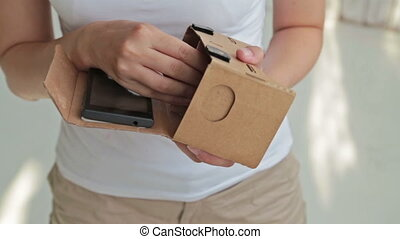 Woman's hands holding Google cardboard. Virtual reality...