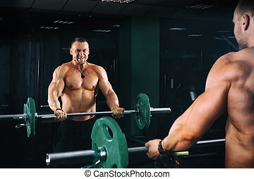 power athletic guy bodybuilder working out biceps with...