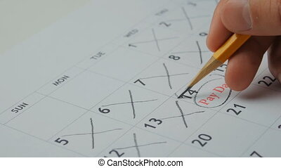 man notes in the calendar that has come payday - guy notes...