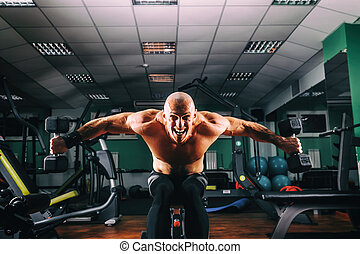 Bodybuider demonstrate crossover exercises in the gym. -...