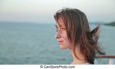 Close up shot of young woman on cruise ship at sunset.