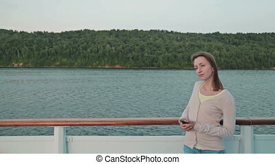Woman with mobile phone looking forward on cruise ship